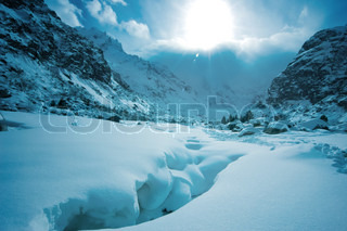 snow covered mountain with sun
