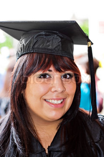 A woman that recently had a university or high school graduation ceremony posing in her cap and gown outdoors