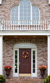The front entrance of a large custom built luxury home in a residential neighborhood