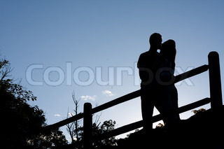 Silhouette of an affectionate couple romantically kissing each other in the early evening hours