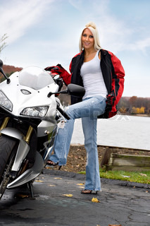 A pretty blonde posing with her motorcycle and riding gear