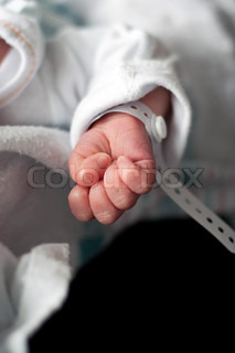 Close up of a newborn infants baby hand and wristband shortly after birth