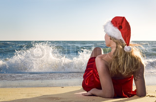 Woman on the beach in santa hat