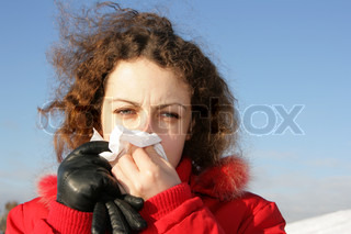 Young woman blowing her nose at tissue