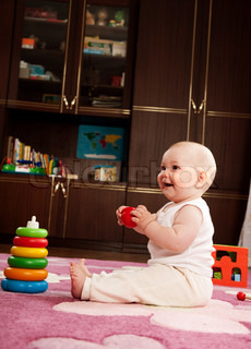 Cute baby girl s playing with toys in playroom