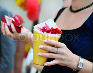 Woman holding yellow paper bag with rose petals