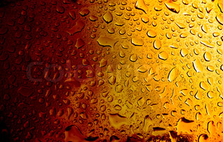 A macro of some water condensation on a glass full of amber colored beer