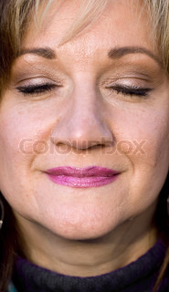 A pretty middle aged woman smiling with her eyes closedShallow depth of field