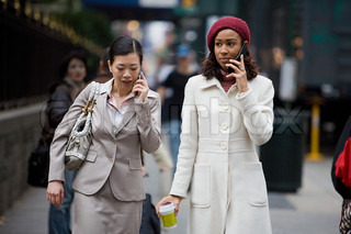 Two business women having conversations on their cell phones while walking in the big city