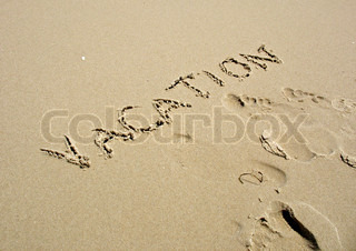 The word VACATION written in the sand along with some footprints