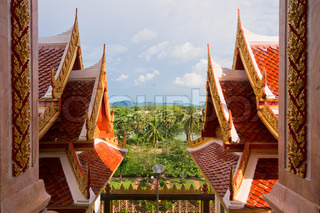 Tiled roofs of asian temple on the background oftropical landscape, Thailand