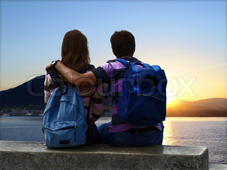 Young couple sitting together on lakeside.
