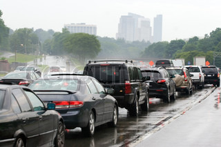 A busy congested highway during rush hour just outside the cityDrivers impatiently wait in traffic in the bad rainy weather