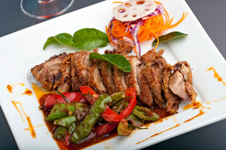 A fresh dish of Thai style roast chile basil duck with mixed vegetables garnished skillfully on a square white plate