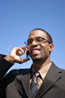 A young business professional talking on his wireless mobile phone
