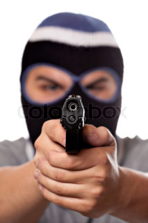An angry looking man wearing a ski mask pointing a black handgun at the viewer Shallow depth of field