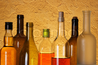 Many bottles of alcoholic beverages over textured background