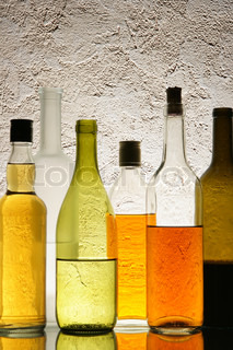 Lots of colorful bottles with alcohol close-up over textured background
