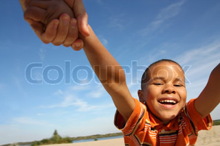 Little black boy playing on the beach, circling hand in hand