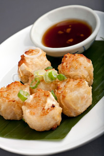 Fried thai appetizers with soy dipping sauce presented on a plate with banana leaf and scallion garnish