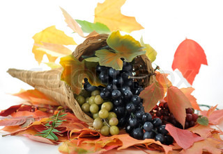 A Fall arrangement in a cornucopia with grape and colorful autumn leaves