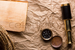 A golden compass and a spyglass laying on an old wrinkled brown paper that can serve as a background for a message or a drawing of a map