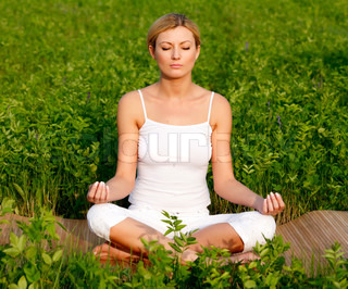 Young beautiful woman in yoga position, outdoors