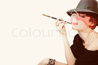 Young beautiful woman with cigarette in mouthpiece inhat with veil on light background
