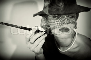 Young beautiful woman withcigarette in mouthpiece in hat with veil
