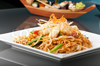 Seafood pad Thai dish of stir fried rice noodles on a square white plate with chopsticks and grated carrot garnish