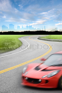 Road scene with a speeding car with motion blur driving down a winding road away from the city skyline