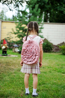 Young school girl with pink backpack poses outdoors