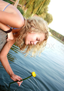 Portrait of the beautiful young girl with blonde and curly hair against trees and river with a yellow lily