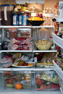 An open refrigerator door showing a full stocked fridge loaded up with food and fresh ingredients
