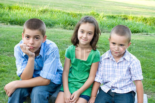 Three kids looking bored and overtired seated on a bench outdoors