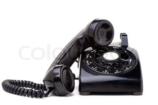 An old black vintage rotary style telephone with the handset off the hook isolated over a white background
