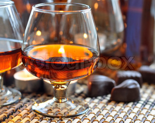 a glass of brandy, sweet and a candle
