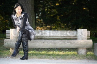 young attractive woman posing on bench in park