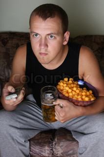 young man watching tv with beer and chips