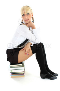 cute schoolgirl sitting on stacked books