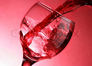 Close-up of pouring wine over red background