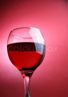 Glass of red wine over red background