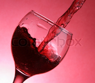 Closeup of pouring wine over red background