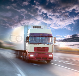 truck on blurry asphalt road over sunset cloudy sky background