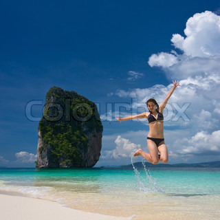 Young cheerful woman is jumping on the beach