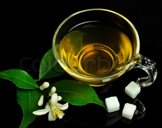 cup of green tea with lemon flowers on a black background