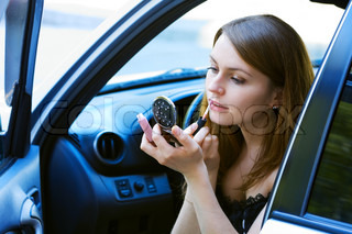 Young woman having make-up in the car