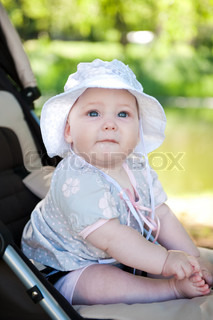 Cute baby in hat is sitting in stroller outdoors