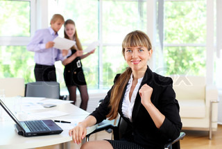young business woman working in office with collegues on background