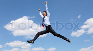 young businessman in a blue suit jumping in the air against blue sky
